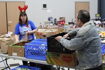 Volunteers and staff pack food into boxes and crates ready to hand out to families in need.  PHOTO BY COLBY HESS