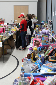 People browse amongst donated toys, with boxes of food awaiting distribution in the foreground. PHOTO BY COLBY HESS